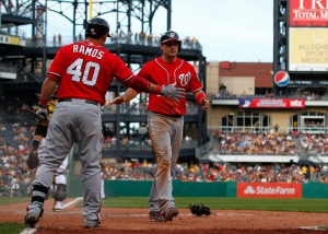 Ryan Zimmerman is greeted at home plate after scoring the game-winning run.