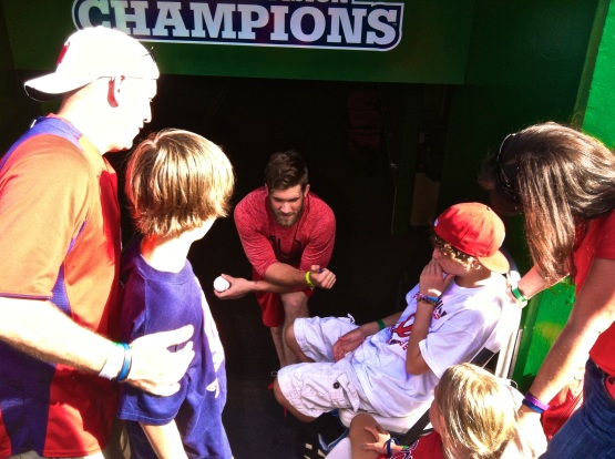 Bryce Harper, center, visiting with Gavin Rupp, right, and his family in the Nationals dugout.