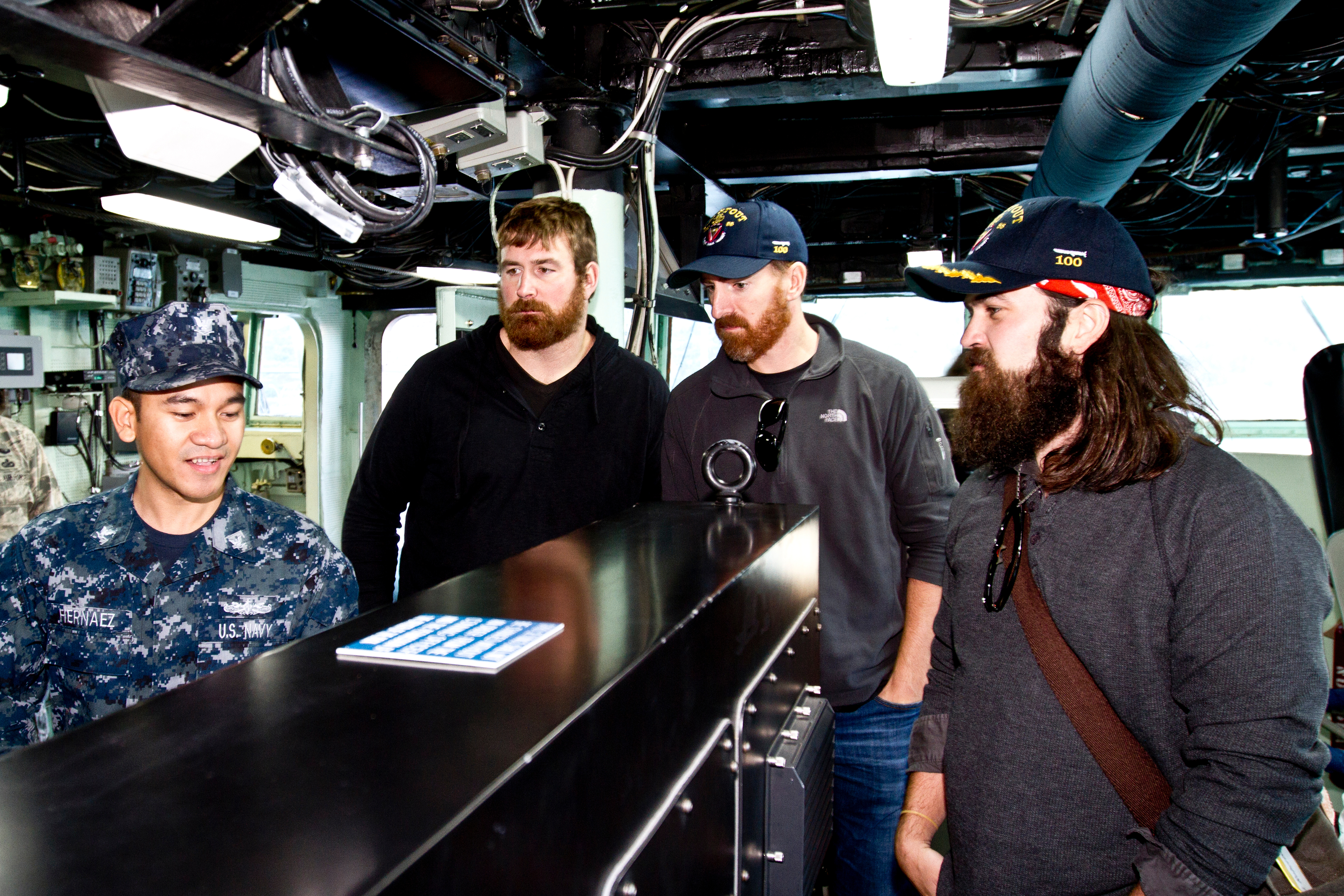 (L to R) Matt Light, Adam LaRoche and Jep Robertson listen to a presentation on the bridge from U. S. Navy QM3 Jerome Hernaez, 26, Waipahu, HI. (Mike Clifton/USO)