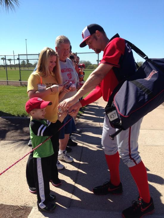 Stephen Strasburg signs autographs for fans.