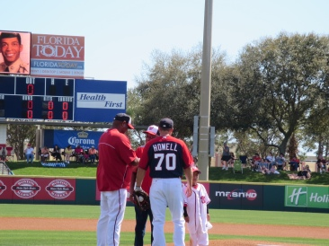 Livan Hernandez and Jeff Howell greet Sergeant Morris and his grandson after their first pitches.
