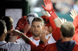 Bryce Harper is congratulated by teammates in the Nationals' dugout.