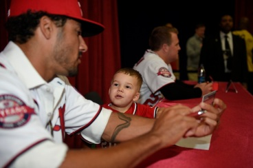 Nationals shortstop Ian Desmond and his son, Grayson, sign autographs for fans.