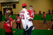 Ian Desmond instructs young Nats fans with one arm and holds his son, Grayson, with the other.
